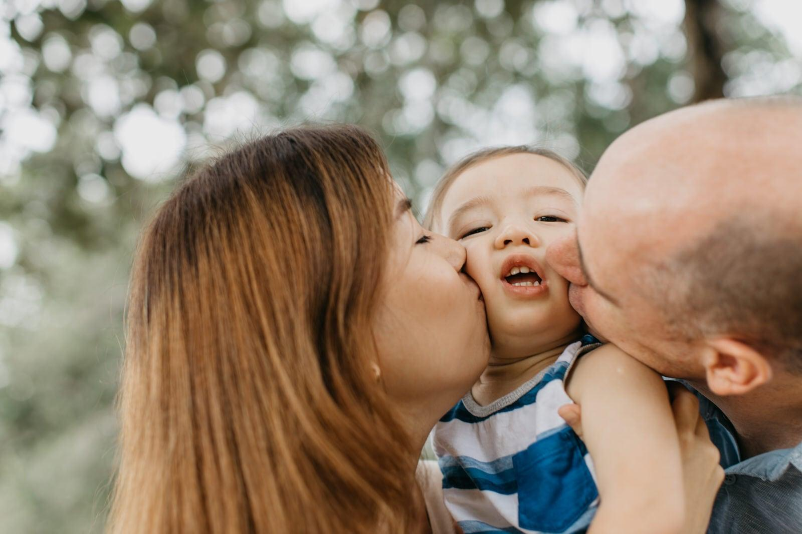 Big kiss Cute little boy with daddy and mommy Damansar Tropical Family Portrait Session in Kuala Lumpur Malaysia
